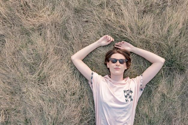Joven descansa sobre la hierba disfrutando de la primavera.