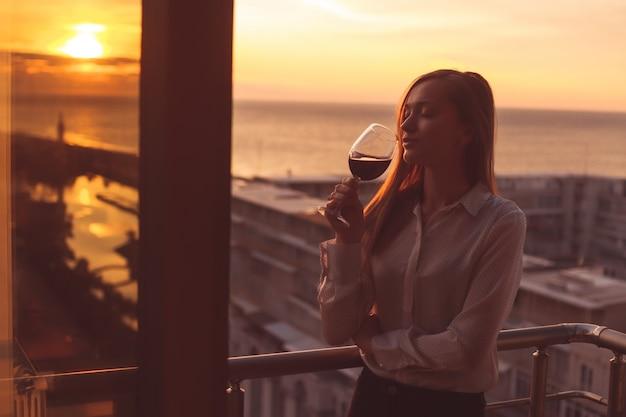 Joven está descansando y bebiendo una copa de vino tinto en el balcón al atardecer en la noche
