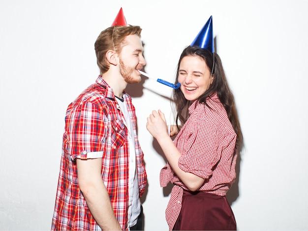 El joven descarado y la mujer se divierten, riendo con gorras de fiesta con tubos aislados