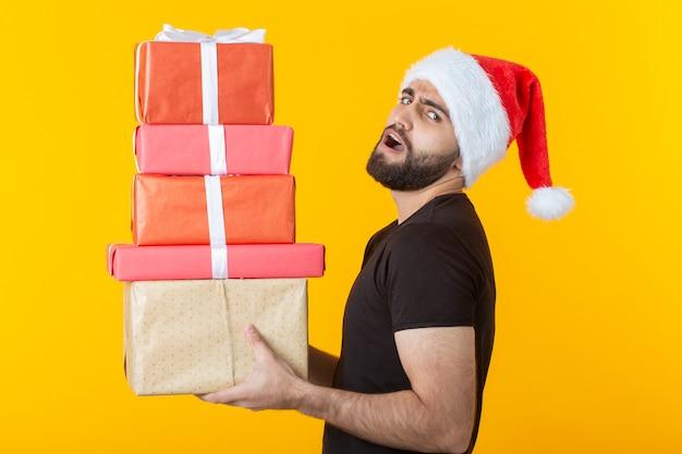 Joven descontento con barba con un sombrero de santa claus tiene cinco cajas de regalo posando sobre un fondo amarillo. concepto de regalos y saludos para navidad y año nuevo.