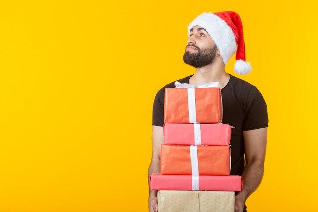 Un joven descontento con barba con un sombrero de santa claus tiene cinco cajas de regalo posando sobre un fondo amarillo con copyspace. concepto de regalos y saludos para navidad y año nuevo.