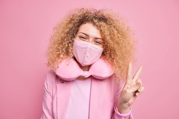 Una joven despreocupada y complacida usa una mascarilla para protegerse del coronavirus, acostumbrada a las medidas de cuarentena, hace el signo de la paz vestida con ropa elegante y usa una almohada para el cuello para sentirse cómodo.