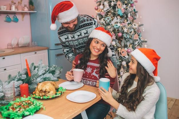 Joven está detrás de la mujer y mira a la esposa. la mujer joven se sienta en tabel y mira a la hija. ambos sostienen tazas. la gente usa ropa festiva.
