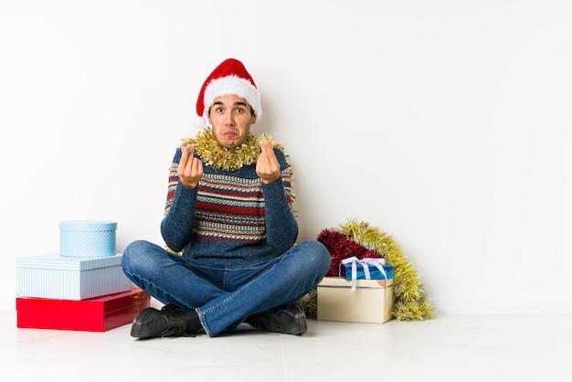 Joven en el día de navidad apunta hacia abajo con los dedos, sentimiento positivo.