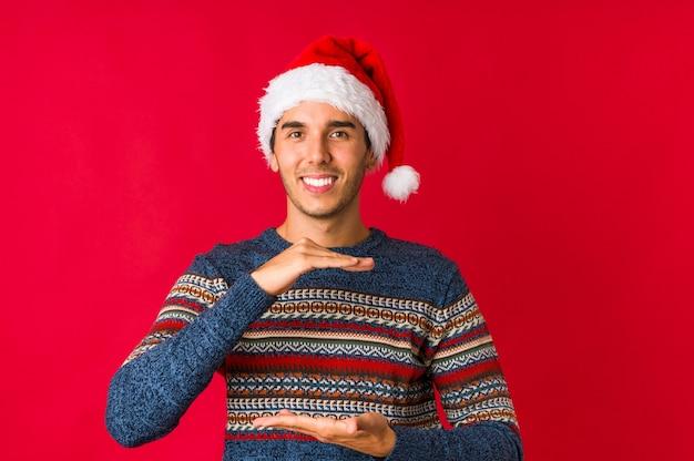 Joven el día de navidad guiña un ojo y tiene un gesto bien con la mano.