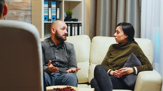 Joven diciéndole a su esposa frente al terapeuta lo que lo hace infeliz con respecto a su relación.