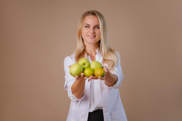 Joven dietista médico sonríe, sosteniendo manzanas verdes.