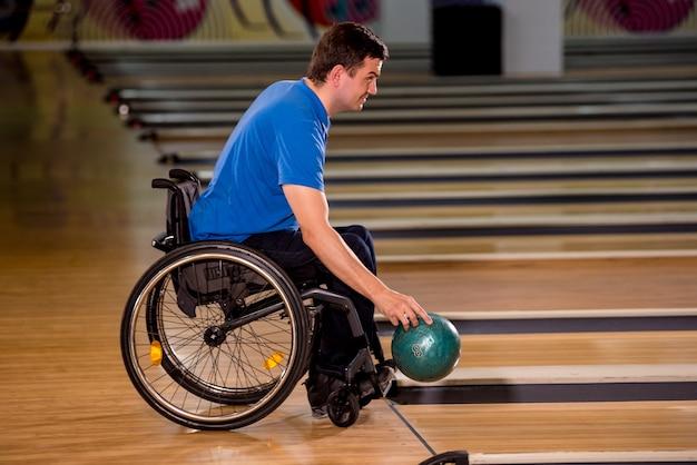 Joven discapacitado en silla de ruedas jugando a los bolos en el club