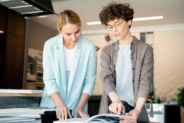 Joven diseñador creativo apuntando a la página del catálogo mientras ayuda al cliente