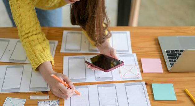 Joven diseñador está dibujando una pantalla de teléfono inteligente y una aplicación.