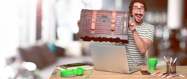 Joven diseñador gráfico loco en un escritorio con una computadora portátil