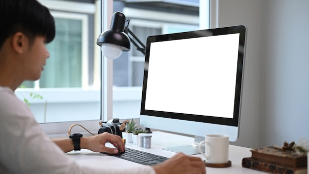 Un joven diseñador gráfico sentado frente a la computadora en el estudio gráfico y trabajando en línea