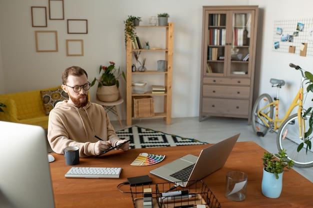 Joven diseñador independiente barbudo que mira la pantalla de la computadora portátil mientras usa la tableta, el lápiz y la paleta de colores para dibujar el logotipo u otra cosa