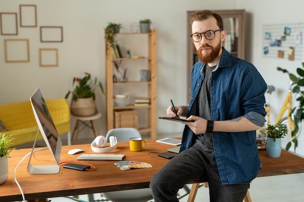 Joven diseñador independiente barbudo sosteniendo un lápiz y una tableta mientras está sentado en la mesa frente a la cámara y dibujando bocetos del nuevo logotipo