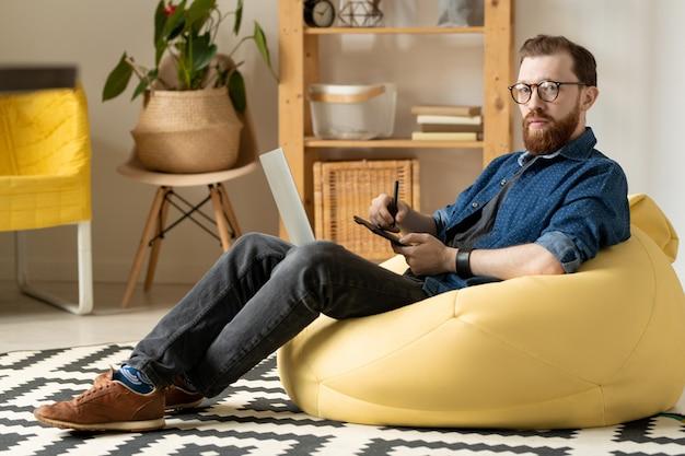 Joven diseñador independiente masculino en anteojos y ropa informal mirándote mientras está sentado en un cómodo sillón y dibuja bocetos del nuevo logotipo