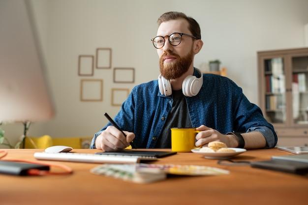 Joven diseñador independiente masculino creativo tomando una copa mientras sostiene el lápiz sobre la tableta y dibuja bocetos del nuevo logotipo o página web