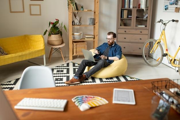 Joven diseñador independiente masculino sentado en un cómodo sillón frente a su lugar de trabajo y dibujando bocetos del nuevo logotipo con lápiz óptico en casa