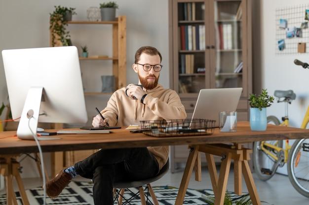 Joven diseñador independiente masculino serio mirando la pantalla de la computadora portátil mientras bebe y usa tableta y lápiz óptico para dibujar un nuevo logotipo