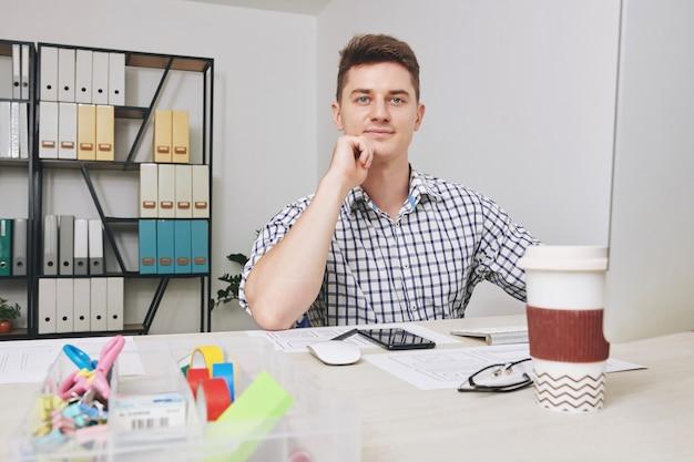 Joven diseñador de interfaz de usuario seguro que trabaja en la computadora en su mesa de oficina y una interfaz de aplicación móvil creativa para el cliente