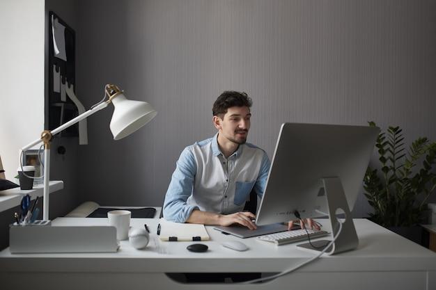 Joven diseñador masculino con tableta gráfica mientras trabaja con com