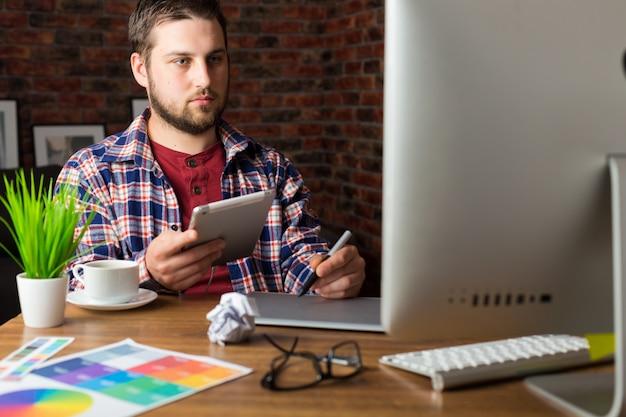 Joven diseñador de perspectiva con tableta gráfica en la oficina moderna