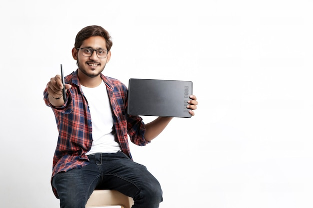 Joven diseñador profesional indio mostrando tableta gráfica con lápiz digital