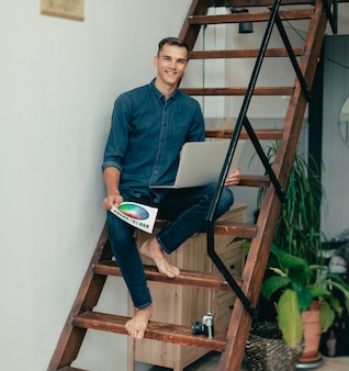 Joven diseñador sentado en los escalones de su casa studio vida doméstica