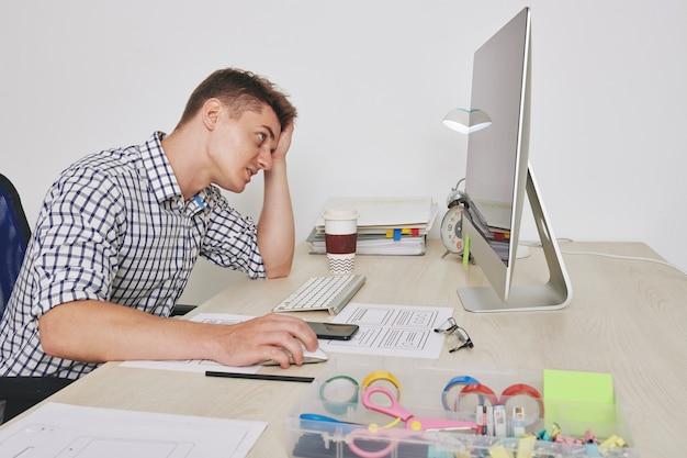 Joven diseñador de ui estresado haciendo correcciones finales en el diseño del sitio web pocos minutos antes de la fecha límite
