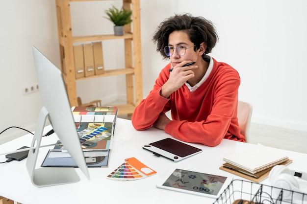 Joven diseñador web pensativo en anteojos mirando la pantalla de la computadora mientras trabaja sobre el nuevo logotipo en casa