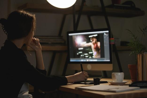 Joven diseñadora concentrada en la noche usando la computadora
