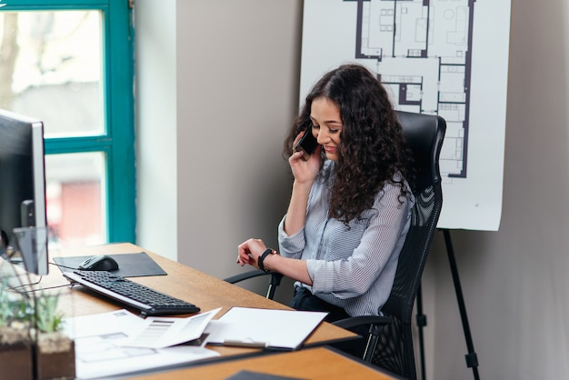 La joven diseñadora de interiores habla por teléfono inteligente y mira el reloj durante la jornada laboral en la oficina moderna.