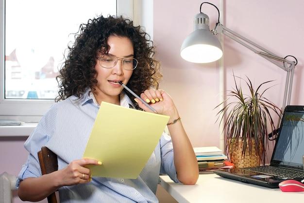 A una joven diseñadora se le ocurre un boceto de ropa y hace bocetos en papel.