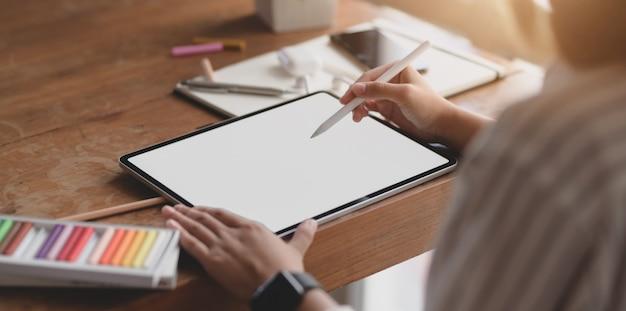 Joven diseñadora profesional femenina que trabaja en la tableta de la pantalla en blanco en su espacio de trabajo