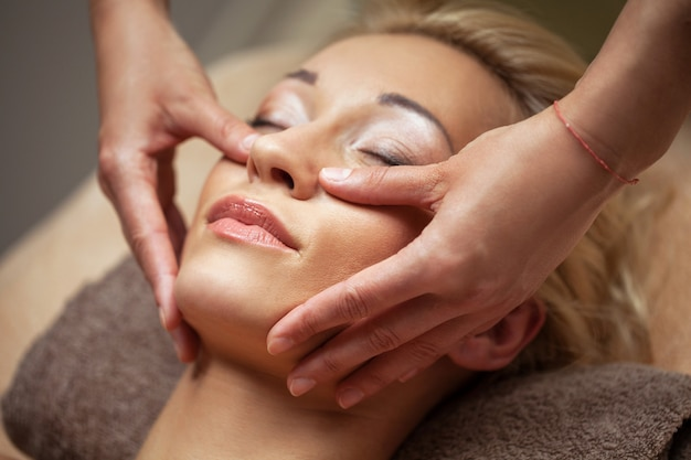 Joven disfruta de un masaje facial en spa