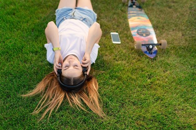 Joven disfruta tumbarse en el césped verde y escuchar música después de montar en su tablero