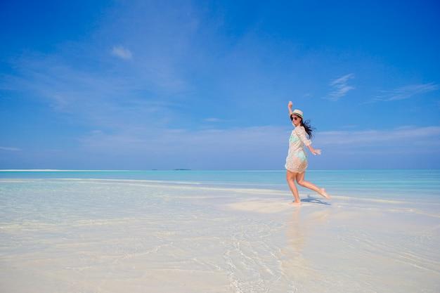 Joven disfruta de vacaciones en la playa tropical en maldivas