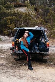 Joven disfrutando de la naturaleza mientras está sentado en el baúl del auto