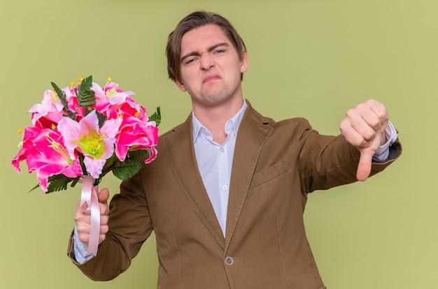 Joven disgustado sosteniendo ramo de flores mostrando el pulgar hacia abajo