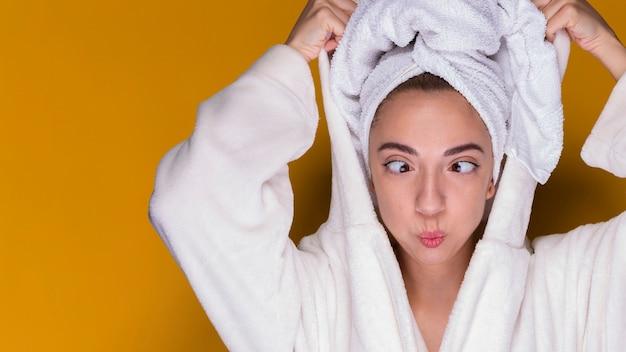 Joven divertida en bata de baño