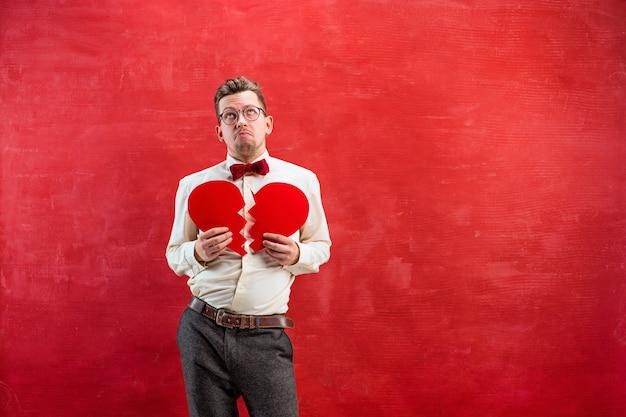El joven divertido con corazón roto abstracto sobre fondo rojo de estudio. concepto - amor infeliz