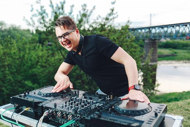 El joven dj-hipster se encuentra detrás de la mesa de mezclas y tiene auriculares.