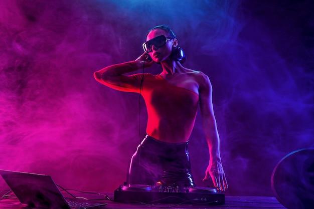 Joven dj sexy con gafas de sol tocando música