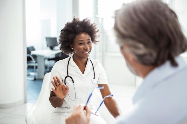 Joven doctora afroamericana y hombre mayor comunicándose en una sala de espera en el hospital.