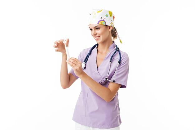 Joven doctora alegre en uniforme con fonendoscopio en el cuello sosteniendo la jeringa en las manos mientras felizmente