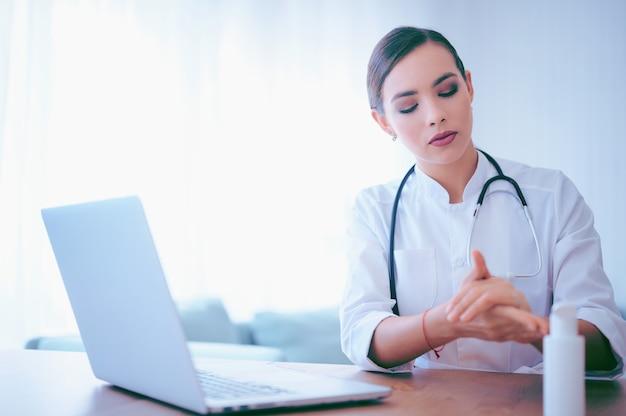 Joven doctora aplica gel antiséptico antes de comenzar la jornada laboral. trabajador del hospital limpiar las manos con desinfectante alcohólico líquido