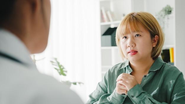 Joven doctora asiática en uniforme médico blanco discutiendo resultados o síntomas con paciente niña