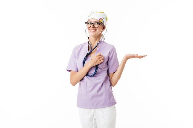 Joven doctora bastante sonriente en uniforme y anteojos sosteniendo felizmente el fonendoscopio