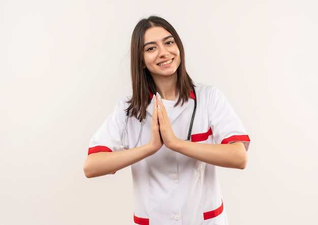 Joven doctora en bata blanca con estetoscopio alrededor de su cuello cogidos de la mano como gesto de namaste sintiéndose agradecido de pie sobre una pared blanca