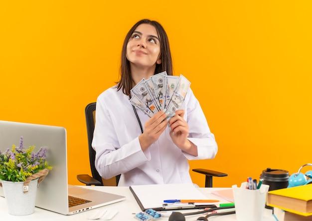 Joven doctora en bata blanca con estetoscopio sosteniendo dinero en efectivo con mirada soñadora, sentada en la mesa con computadora portátil y documentos sobre pared naranja
