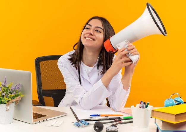 Joven doctora en bata blanca con estetoscopio sosteniendo megáfono sonriendo con cara feliz sentado en la mesa con computadora portátil y documentos sobre pared naranja